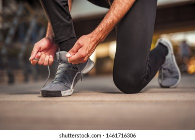 Man tying running training shoes. A person jogging outdoors on a sunny day. Focus on a side view of two human hands reaching down to a grey athletic shoe.
