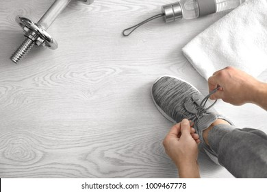 Man tying shoe laces in gym, top view