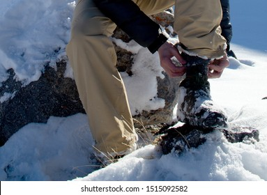 Man tying shoelaces on hiking boots in the winter