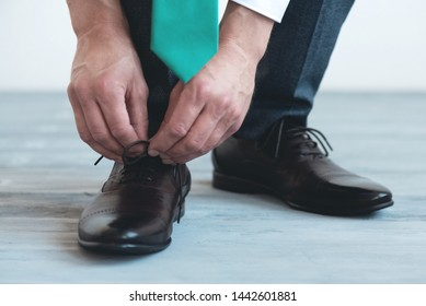 Man is tying shoelaces on his brown leather shoes on a blue wooden floor background.