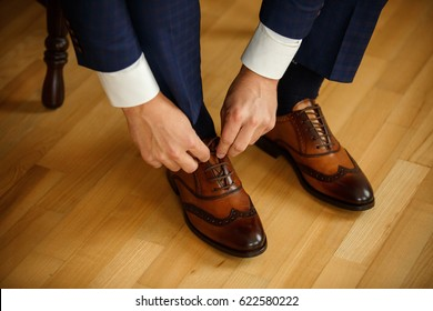 Man tying shoes laces on the wooden floor