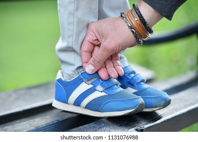 man tying velcro snickers on child