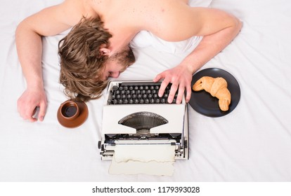 Man with typewriter coffee lay bed. Man sleepy lay bedclothes while work. Writer used old fashioned typewriter. Workaholic fall asleep. Author tousled hair fall asleep while write chapter top view.