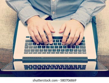 Man is typing with a modern laptop in his lap. Casual clothes. Hipster. Image has a vintage effect applied. Image taken from above.