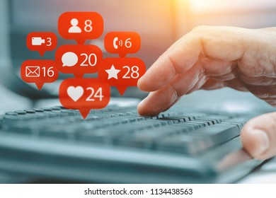 man typing and notification icons of social network flying over keyboard