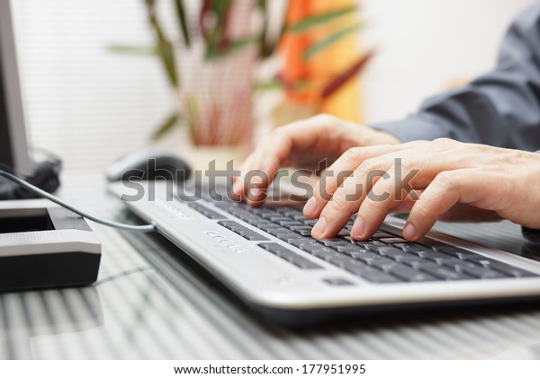 man  is typing on keyboard at home