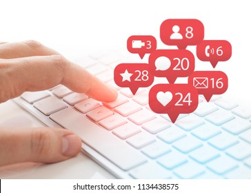 man typing on keyboard and notification icons of social network flying over keyboard