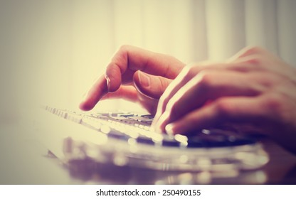 man typing on a keyboard with a retro instagram filter (shallow depth of field)