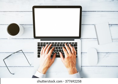 Man typing on a laptop with a blank screen, mock up