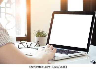 Man is typing on laptop computer keyboard which has white blank mock up screen.