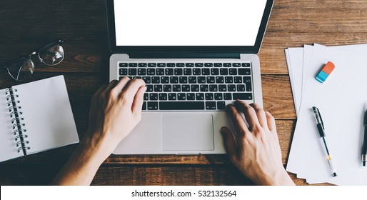 A man is typing on a laptop mockup on messy wood office table.