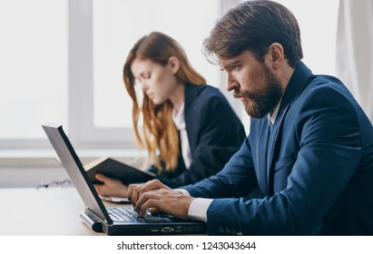 man typing text on a laptop and an employee in the background