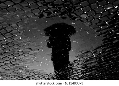 man with umbrella reflected in the water