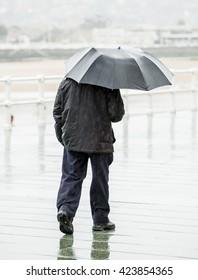 Man with umbrella walking around the city