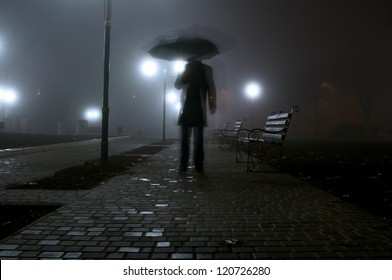 man with umbrella walking in the light of lanterns in the night park