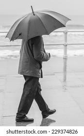Man with umbrella walking through the city