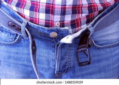 Man unbuckled his belt and unbuttoned jeans by hands after having a heavy dinner. He pats his stomach. He is wearing jeans and plaid shirt, waist closeup.