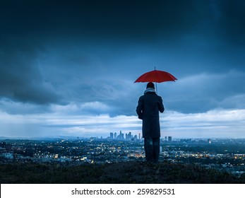 Man under red umbrella overlooking stormy Los Angeles cityscape from Hollywood Hills at twilight.