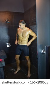 Man under shower looking on mirror. Male beauty and cosmetics concept.