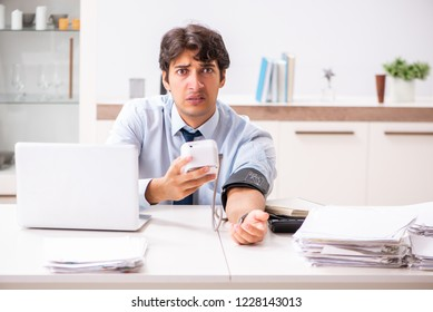 Man under stress measuring his blood pressure