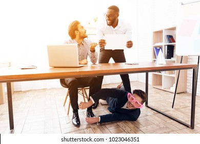 A man under the table to tie laces to his business colleague. This is a joke on April 1. They joke on their friend. They have a good mood.