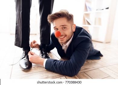 A man under the table to tie laces to his business colleague. This is a joke on April 1. He jokes on his friend. He has a good mood.