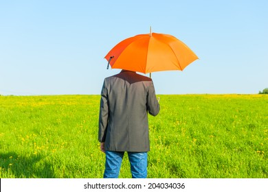 man under an umbrella on a sunny day in the field