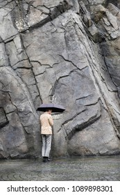 Man under umbrella wearing casual suit facing dead end stone wall in the rain. Conceptual image of facing life crisis problem