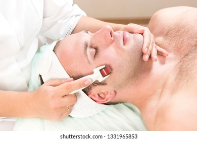 The man undergoes the procedure of medical micro needle therapy with a modern medical instrument derma roller.