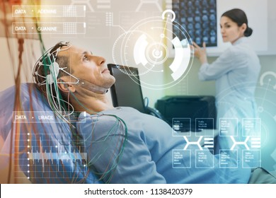 Man undergoing EEG. Serious calm man looking at the ceiling and keeping silent while undergoing electroencephalography