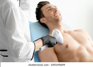 Man undergoing hair removal procedure with photo epilator in salon