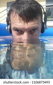 man underwater listen music with head-phones