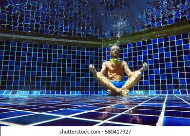 Man underwater portrait in yoga position inside a swimming pool in the lotus position