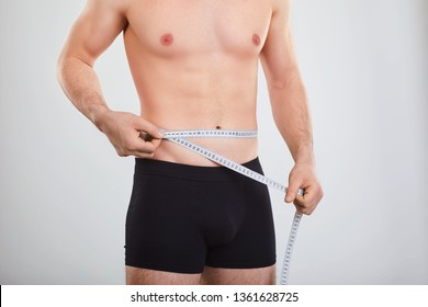 A man in underwear measures the waist with a centimeter