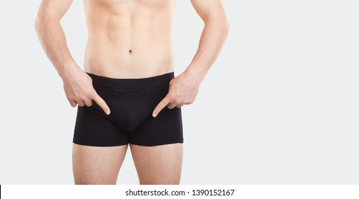 A man in underwear points his finger at the penis.