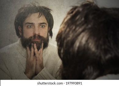 Man unhappy looking in the old mirror