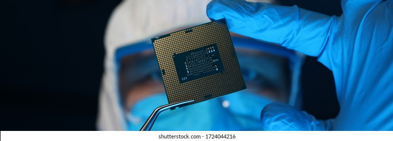 Man in uniform holds microprocessor with forceps. Software-controlled device for processing information. Repair microprocessor electronics electrical equipment. Engaged in chip implementation