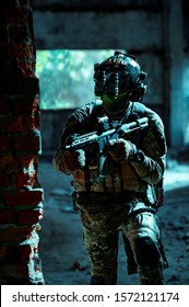 Man in uniform with machine gun and night-vision device move inside broken building. Airsoft soldier in night building