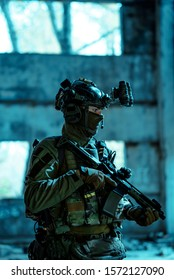 Man in uniform with machine gun and night-vision device inside broken building. Airsoft soldier in night building, side view