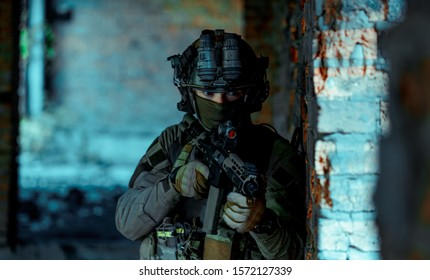 Man in uniform with machine gun and night-vision device stand beside broken wall. Closeup airsoft soldier in night building. Vertcal photo