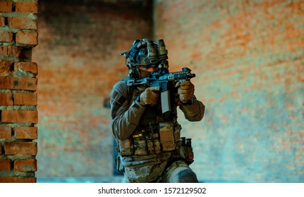 Man in uniform with machine gun and night-vision device, move in broken building. Airsoft soldier Aims at the sight in building. Horizontal photo