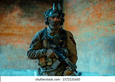 Man in uniform with machine gun and night-vision device in broken building. Airsoft soldier Aims at the sight in building. Horizontal photo