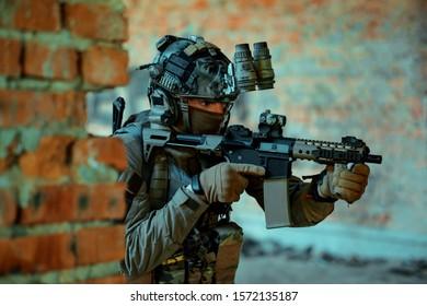 Man in uniform with machine gun and night-vision device, move in broken building. Airsoft soldier Aims at the sight in building.