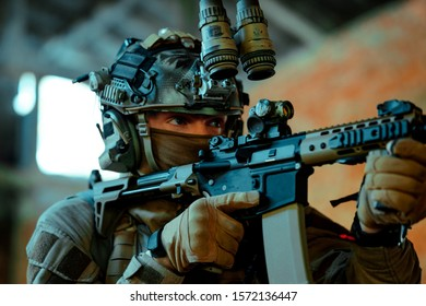 Man in uniform with machine gun and night-vision device, move in broken building. Closeup airsoft soldier aims at the sight in building.