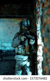 Man in uniform with machine gun and night-vision device stand beside broken wall. Airsoft soldier in night building. Vertcal photo