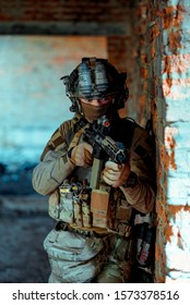 Man in uniform with machine gun and night-vision device stand beside broken wall. Closeup airsoft soldier in night building. Vertcal photo.
