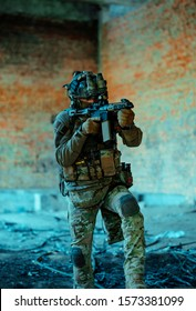 Man in uniform with machine gun and night-vision device, move in broken building. Airsoft soldier Aims at the sight in building. Vertical photo
