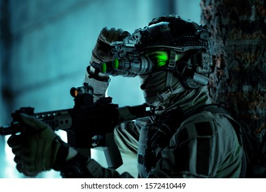 Man in uniform with machine gun and turned on night vision device inside broken building. Closeup airsoft soldier with green light on face in night building