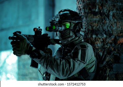 Man in uniform with machine gun and turned on night vision device inside broken building. Airsoft soldier with green light on face in night building