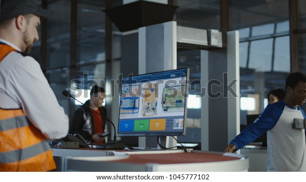 0856d8db Man in uniform watching monitor with x-ray of baggage checking passengers  in airport.